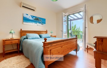 Master bedroom with king size bed on the first floor with access to shared balcony