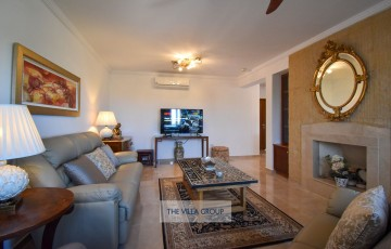 Living area with lovely decor, comfortable seating, a feature wall and decorative fireplace
